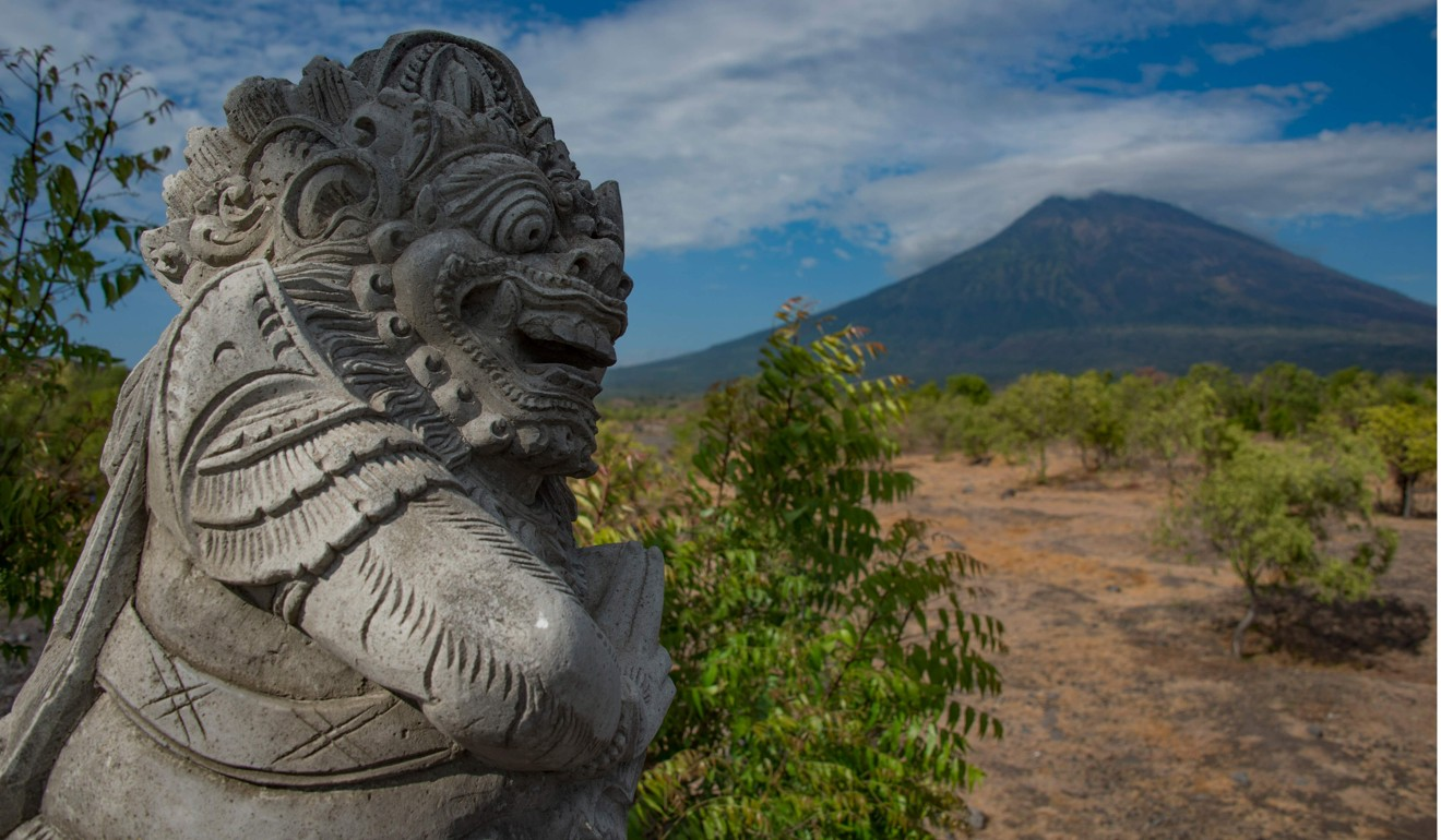 A statue is placed on the roadside in Karangasem, on Bali island, as Mount Agung volcano is seen in the background.