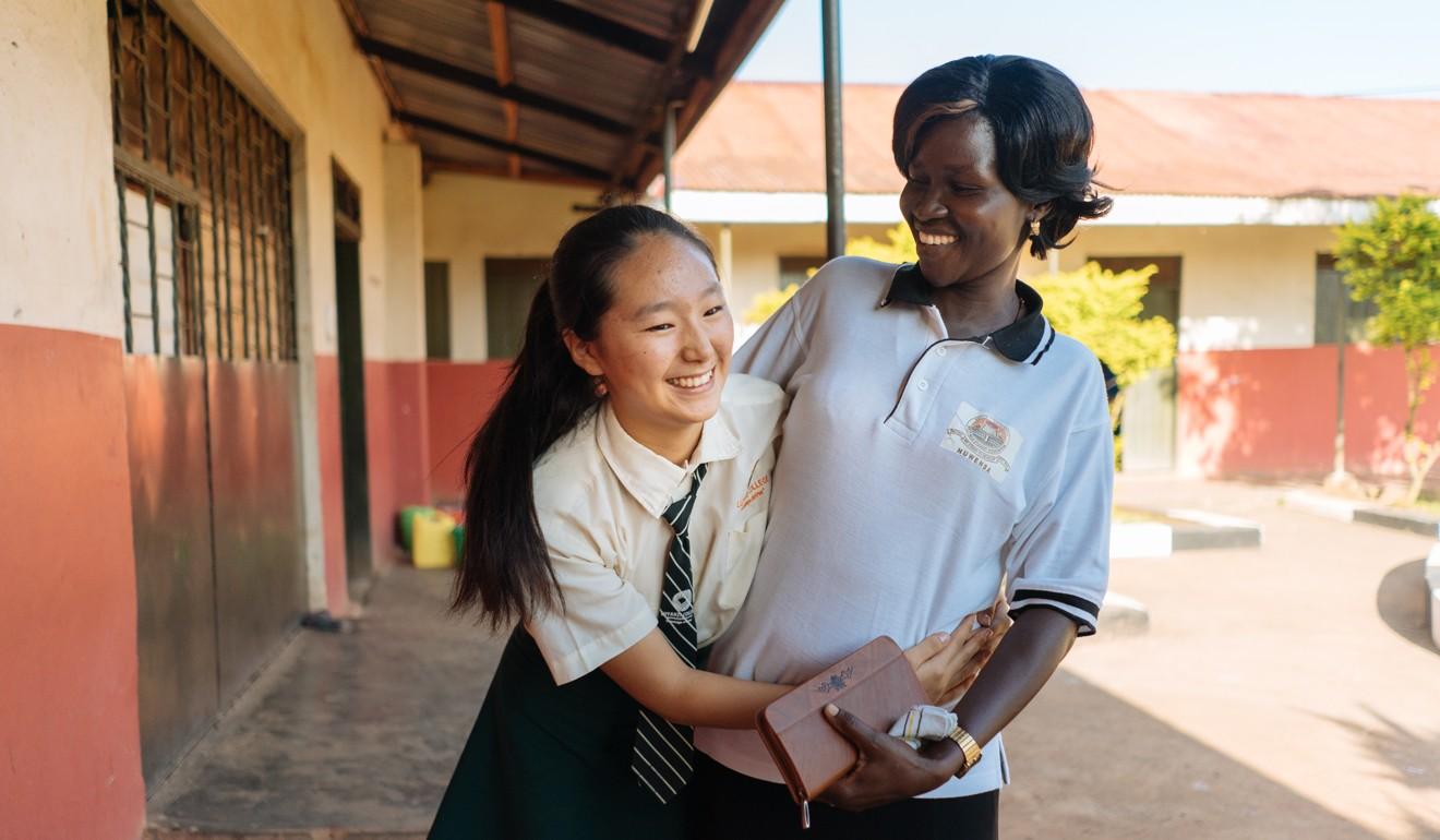 One of the few Chinese students at Luyanzi College bonds with her Ugandan geography teacher between lessons.