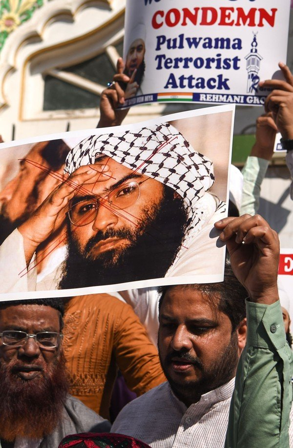 Indian protesters hold up a scratched photo of Jaish-e-Mohammad chief Masood Azhar in Mumbai the day after the Kashmir attack. Photo AFP