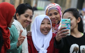 Erwiana Sulistyaningsih (white headscarf, centre), on a return visit to the city. Photo: Felix Wong