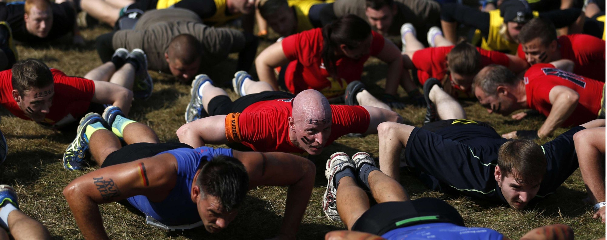 """Participants warm up for the """"Tough Mudder"""" endurance event series in Arnsberg September 6, 2014. Competitors who took part in the endurance event saw themselves having to overcome various military style obstacles. REUTERS/Ina Fassbender (GERMANY - Tags: SOCIETY SPORT)"""