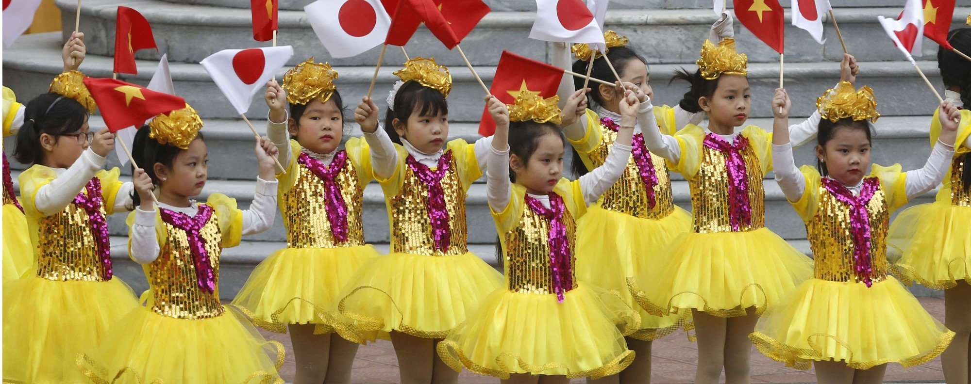 Vietnamese children wave Japanese flags for Emperor Akihito's visit. Photo: AP