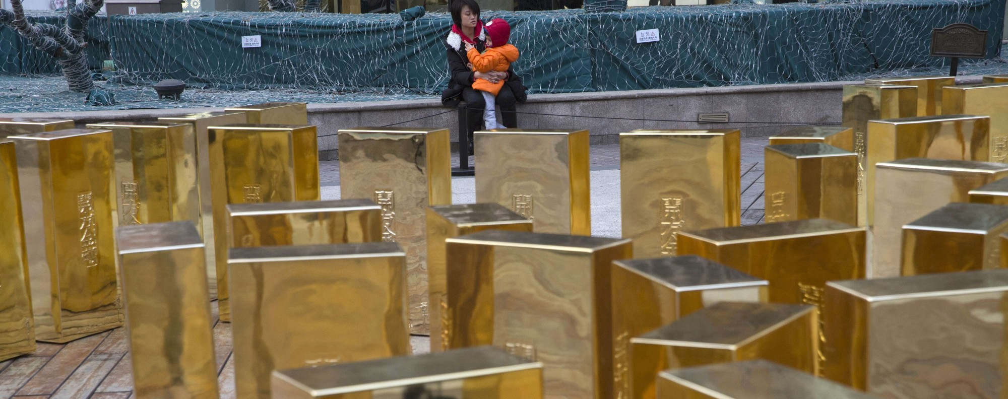 A woman and child near gold bar replicas in Beijing. Photo: AP