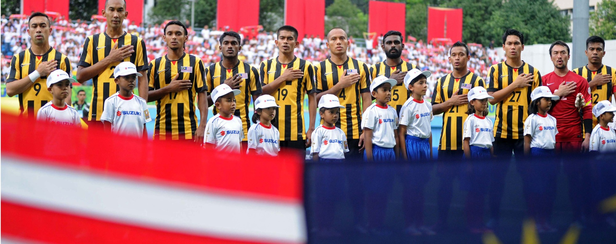 Malaysian footballers sing their national anthem. Photo: AFP