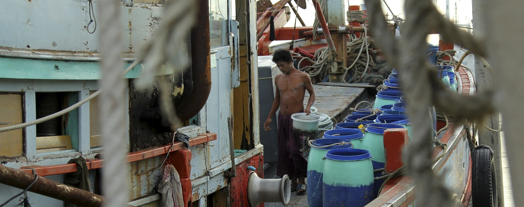A migrant from Myanmar cleans a fishing vessel in Mahachai. Photo: Laura Villadiego