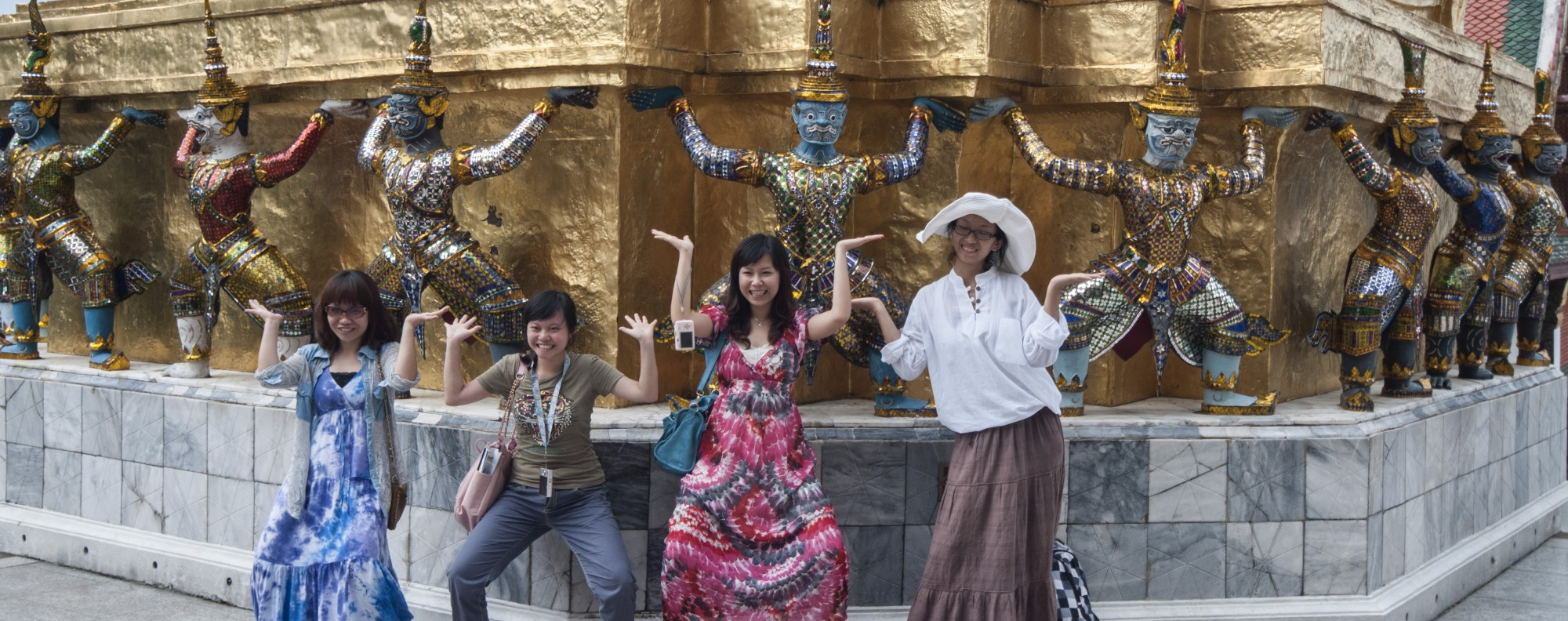 Chinese tourists pose in front of Bangkok's Emerald Buddha Temple.