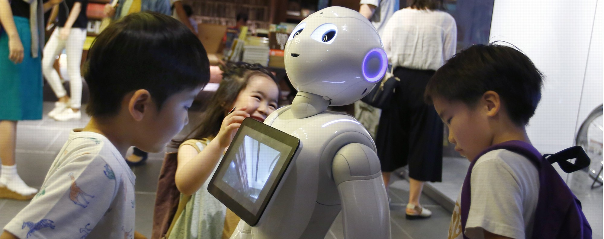 Children surround SoftBank's Pepper robot in Tokyo. Photo: AP