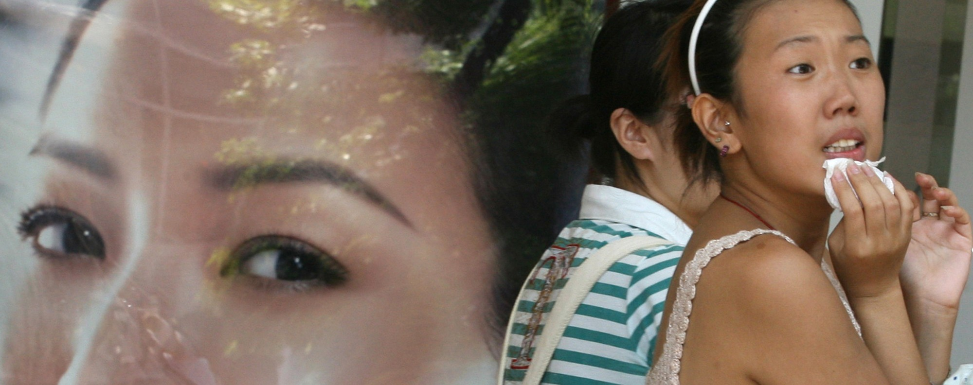 A woman in Shanghai walks past an advert for skin-whitening products. Photo: AFP