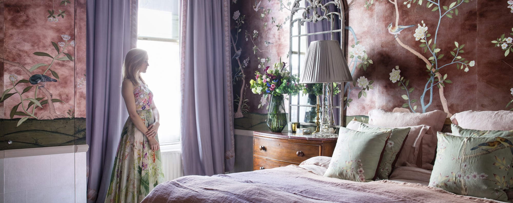 """At dusk the walls shimmer like antique silver making the room the loveliest in the world."" The wallpaper is called Badminton, hand-painted from de Gournay. The marble top drawer Hannah remembers her father bought in a junk shop and renovated when she was little. Her dress is from Jenny Peckham, sewn in silk from de Gournay, that also make fabric. 