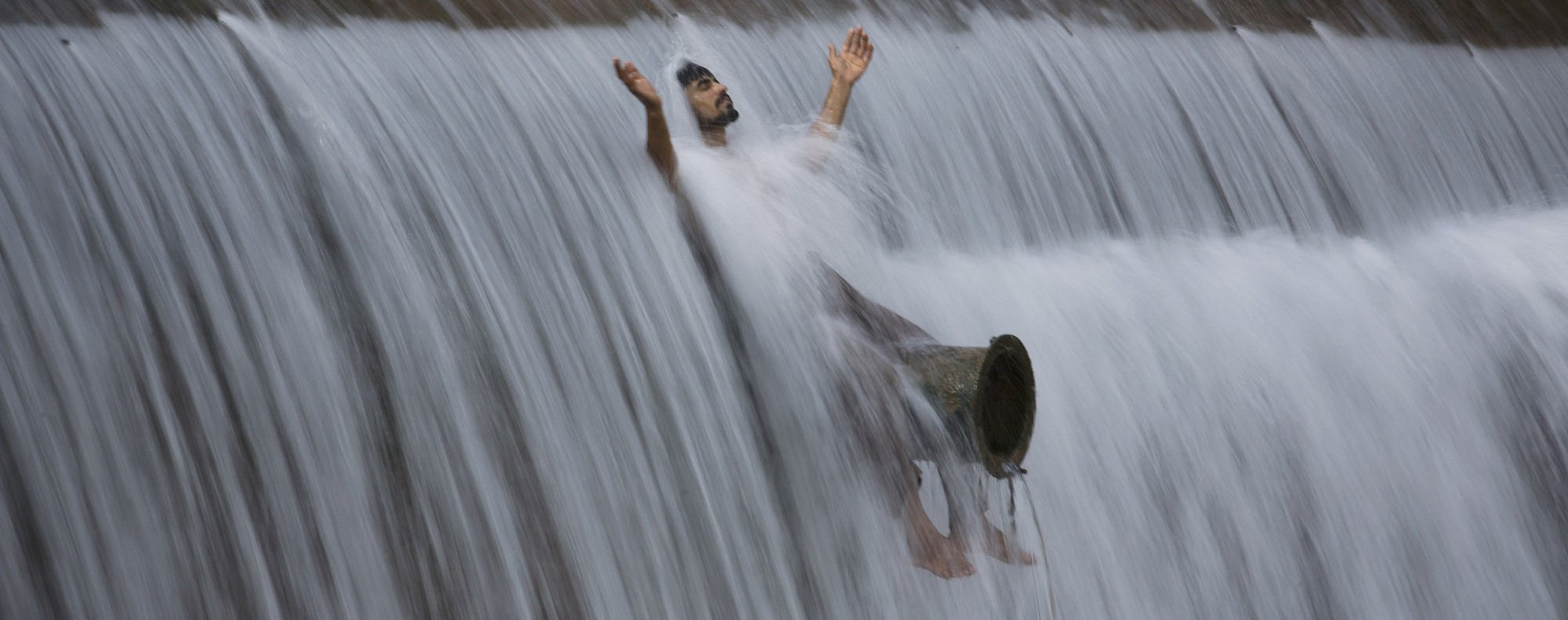 A man cools off at a dam on the outskirts of Islamabad, Pakistan. Photo: AP