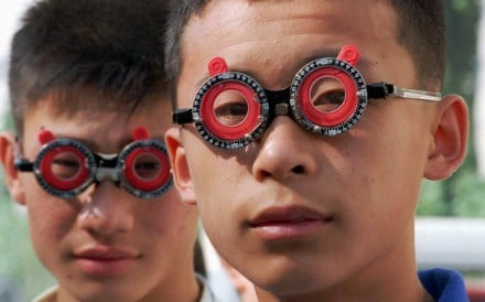 Chinese students have their eyesight tested with temporary lenses by an optician. Photo: Reuters