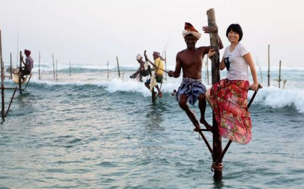 A Chinese tourist poses for a photo with a fisherman in Sri Lanka. Photo: Xinhua