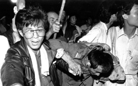 A captured tank driver is helped to safety by students in Tiananmen Square, Beijing, as the crowd attempts to beat him on June 4, 1989. Picture: Reuters