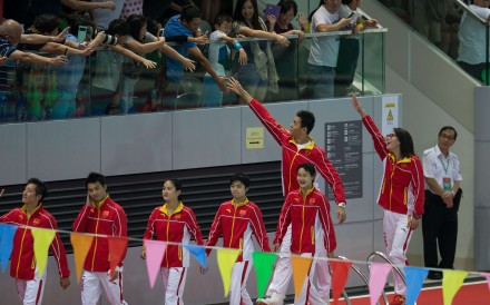 Hong Kong fans reach out to members of China's Olympic team at Victoria Park swimming pool on August 28. The 45 athletes in the 64-member delegation on a three-day visit included the wildly popular bronze medallist swimmer, Fu Yuanhui. Photo: EPA
