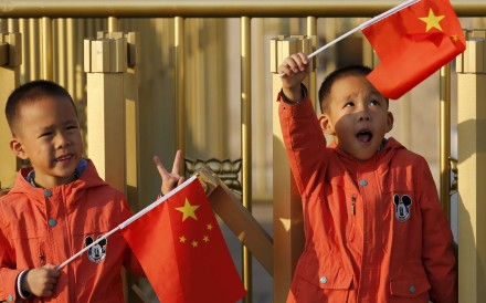 Twin boys hold China's national flags on the Tiananmen Gate in Beijing. Photo: Reuters