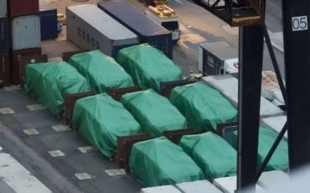 Nine Singapore-made Terrex armoured troop carriers lie under tarpaulin last November 24, after being seized at the Kwai Tsing container terminals the previous day while in transit from military exercises in Taiwan. Photo: AP