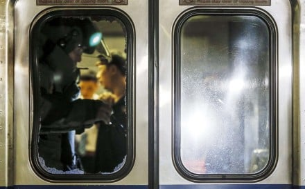 epa05413187 A member of a bomb squad is seen through a broken glass door of a train carriage after an explosion at Songshan train station in Taipei, Taiwan, 07 July 2016. According to news reports, the number of injured passengers might be up to 13 or 20, with some of them being sent to hospital by ambulance. Ongoing investigation is being conducted to find the cause of the explosion. EPA/RITCHIE B. TONGO