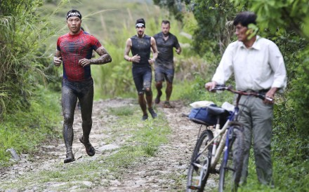 A man on a bicycle watch participants pass through during the Asia-Pacific Spartan Race series in Kam Tin. Photo: Edward Wong