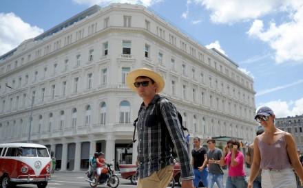 Tourists walk near the Manzana Kempinski Hotel, the first luxury five star plus tourist facility in Cuba. Photo: AFP