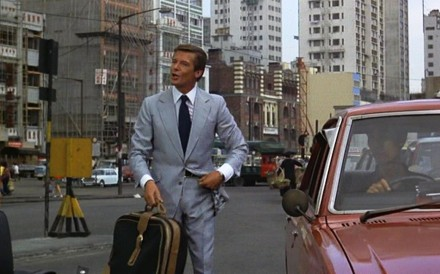 Roger Moore as 007 in a Hong Kong Island street scene in Man with the Golden Gun. Western Market in Sheung Wan is in the background.