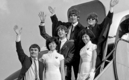 Paul McCartney, George Harrison, John Lennon and Jimmie Nicol (standing in for an unwell Ringo Starr) wave to fans as they arrive at Kai Tak airport in Hong Kong on June, 8, 1964.