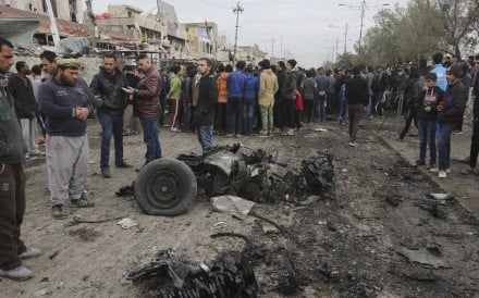 Citizens inspect the scene after a car bomb explosion at a crowded outdoor market in Sadr City, Iraq, on Jan 2. A suicide bomber blew up his explosives-laden vehicle, killing at least a dozen people, amid a fierce regional fight against the Islamic State group. Photo: AP