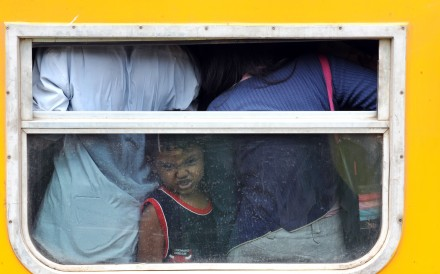 A young passenger is squeezed into an economy carriage at the Jakarta train station as her family returns to their home provinces to celebrate Eid al-Fitr, marking the end of Ramadan. Photo: AFP