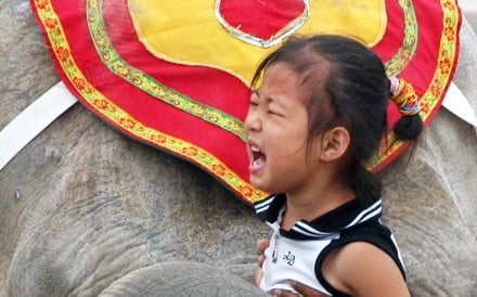 A little girl cries while taking a photo with an elephant during an animal performance at a zoo in Taiyuan. Photo: Reuters