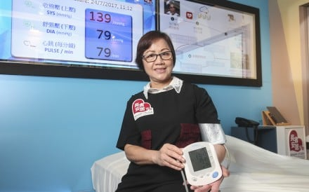 User Ho Yuk-ling demonstrates one of the devices at the show flat which can automatically upload blood pressure data. Photo: K. Y. Cheng