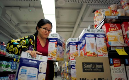 Chinese daigou shopping agent Na Wang selects an Australian breakfast cereal product during a shopping trip for Chinese customers at an Australian supermarket in Sydney. Photo: Reuters