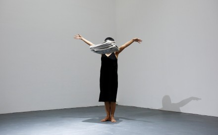 Performance artist Yi Fei drops a pile of newspapers as she performs her piece No News at the OPEN international performance art festival. Photo: Reuters
