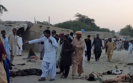 People gather at the blast site in southwest Pakistan where scores were killed in a suicide bomb attack. Photo: Xinhua