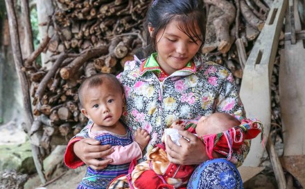 Bang, 16, with her two young children, in Ha Giang, Vietnam. The school dropout spends her days taking care of the family, as a lack of education prevents her from finding a way out of poverty. Photo: Yuki Chang/Plan International Hong Kong