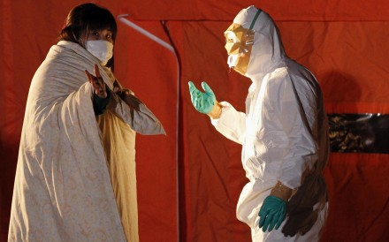 An official in protective gear talks to a woman from the evacuation area near the Fukushima nuclear plant in Koriyama in March 2011. Photo: Reuters
