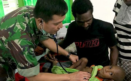 A military doctor treating a Papuan child in the remote Asmat region of Papua, Indonesia. Photo: AFP