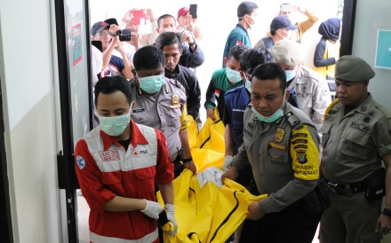 Indonesian police and ambulance crew carry the body of a victim of the bus crash. Photo: AFP