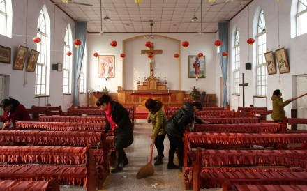 Members of the congregation clean an unofficial Catholic church in Hebei province, after a Sunday service in December 2016. Photo: Reuters