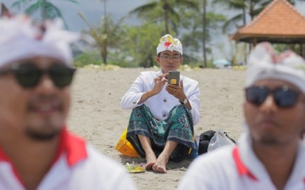A Balinese Hindu uses his mobile phone on a beach during a Melasti purification ceremony, ahead of the holy day Nyepi, in Gianyar, Bali. Photo: Reuters