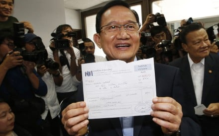 Thailand's former prime minister Somchai Wongsawat shows receipt after registering his membership to Pheu Thai Party in Bangkok. Photo: AP