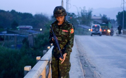 A militiaman linked to the Malaysian army stands on a bridge in Muse. China on Sunday condemned fighting on its border between Myanmar forces and ethnic rebels that left 19 people dead, most of them civilians. Photo: AFP