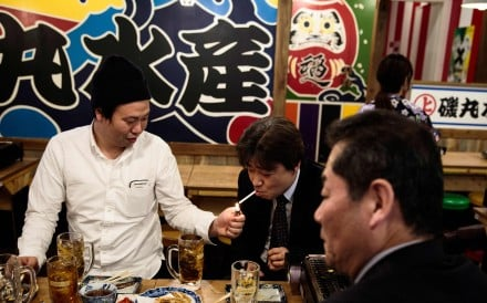 A man lights a cigarette for his friend during lunch in a Tokyo restaurant. A Japanese lawmaker jeered during a lung cancer patient's testimony concerning legislation restricting indoor smoking. Photo: AFP