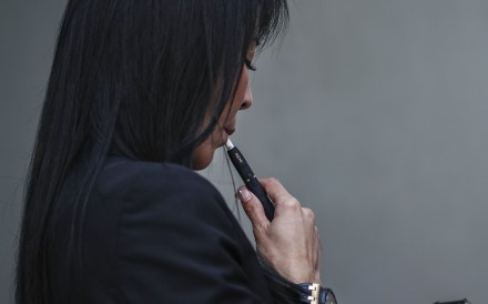 A woman smokes an electronic cigarette in Mong Kok. The Hong Kong government is proposing to regulate the sale of e-cigarettes and heat-not-burn products in the same way as conventional cigarettes. Photo: Edward Wong