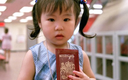A two-year-old girl clutches her passport at the Immigration Department in 1995. Parents were signing their children up in droves to obtain British National (Overseas) passports ahead of the city's return to Chinese rule in 1997. Photo: SCMP