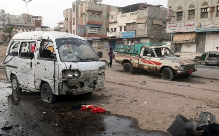 People walk past damaged cars at the entrance of Al-Thawra hospital. Photo: AFP