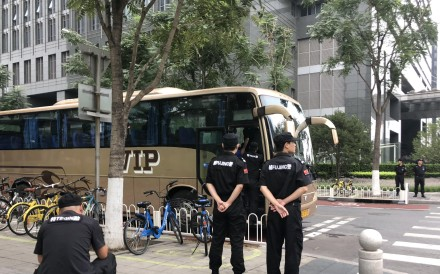 Police, plain clothes police and security personnel along with parked buses, are pictured at the Financial Street in downtown Beijing on 6 August, 2018. Photo:SCMP / Simon Song