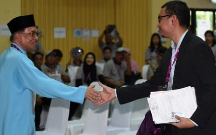 President of the People's Justice Party and leader of the Pakatan Harapan coalition Anwar Ibrahim (left) shakes hands with independent candidate Saiful Bukhari Azlan after submitting his documents at the nomination centre for a by-election in Port Dickson on September 29, 2018. Photo: AFP
