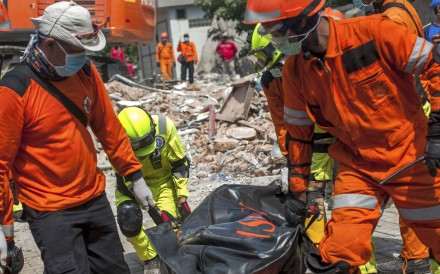 Rescuers recover the body of an earthquake victim from the ruins of the collapsed Roa Roa hotel in Palu. Photo: AP