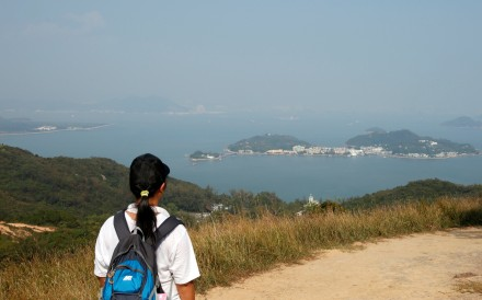 A hiker on Lantau looks across at Peng Chau and other nearby islands. The Hong Kong government aims to reclaim 1,700 hectares off Lantau Island to address housing and other land needs. Photo: Reuters