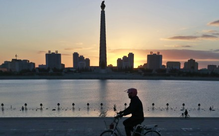 In Pyongyang, a man rides his electric bike near the Tower of the Juche Idea. Photo: AP