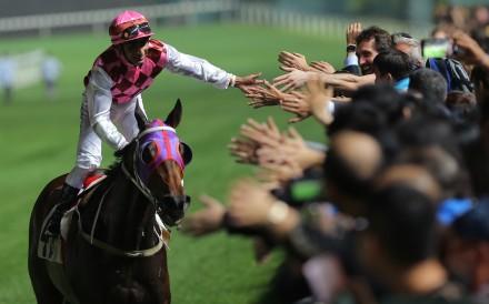 Karis Teetan high fives fans after winning aboard Brave Legend. Photos: Kenneth Chan